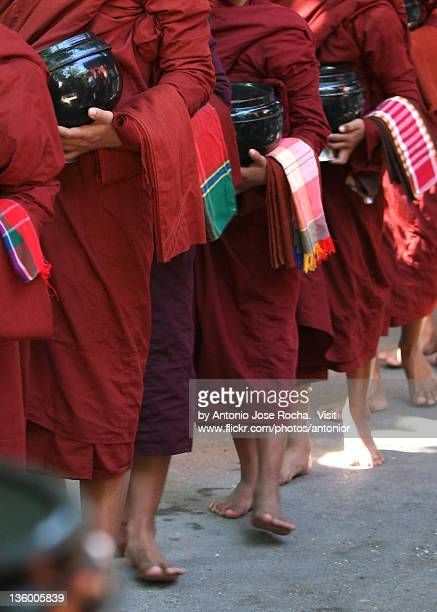 Barefoot monks with pots queuing for lunch
