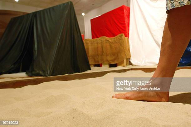 A barefoot patron enjoys the sandfilled installation 'Eden' by Hlio Oiticica at 'Tropiclia A Revolution in Brazilian Culture' an exhibit that...