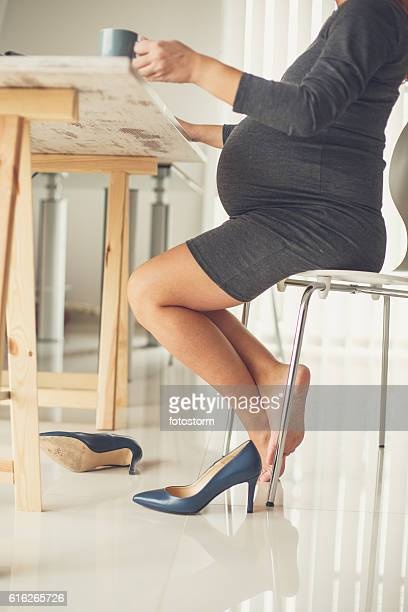 Barefoot pregnant business woman in office drinking coffee