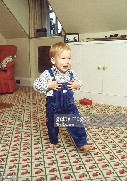 Barefoot Prince Harry Takes His First Steps At Home In The Playroom In Kensington Palace On The Shelf Behind Is A Photograph Of Him With His Mother...