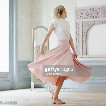 Barefoot woman dancing in front of a mirror