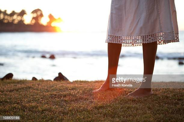 A barefoot woman in a dress walks on grass above the sea at sunset.