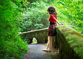 Barefoot woman leans against mossy wall in forest