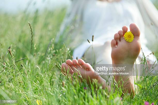 Barefoot woman sitting in grass, holding dandelion flower between toes