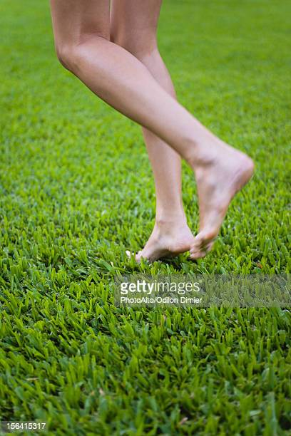 Barefoot woman walking on grass, low section