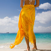 unrecognizable and barefoot woman in white bikini wrapped in orange sarong standing on a beach in the Caribbean and enjoying the ocean view