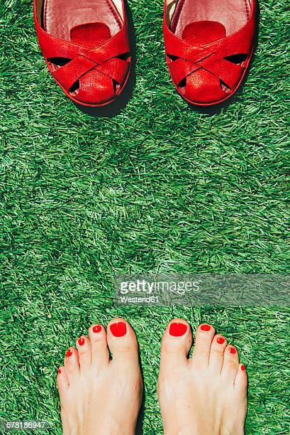 Barefoot women with nails painted red next to a pair of red shoes, on the green grass