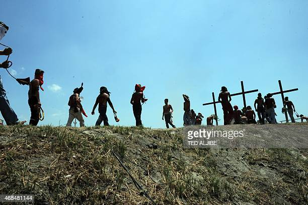 Barefooted penitents march to a hill as they flagellate themselves to fulfill their vows during the observance of Lent in the village of Cutud San...