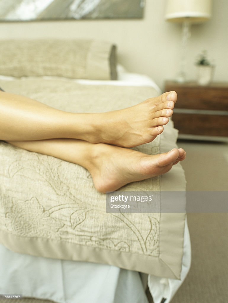 Barefooted woman lying on bed,low section : Stock Photo