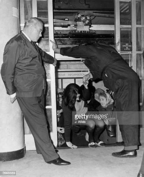Bargain hunters at Barkers of Kensington department store in London getting more than they bargained for when they have to be helped out of a lift...
