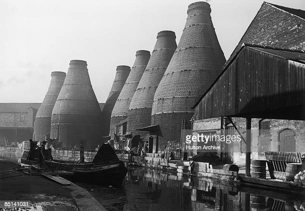 A barge on a canal running alongside bottle kilns belonging to potteries in StokeonTrent Staffordshire circa 1948
