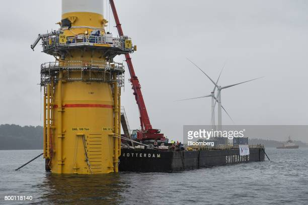 A barge operates at the base of an offshore floating wind turbine during assembly in the Hywind pilot park operated by Statoil ASA in Stord Norway on...