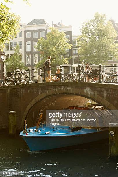 Barge passing under canal bridge, Amsterdam, Netherlands