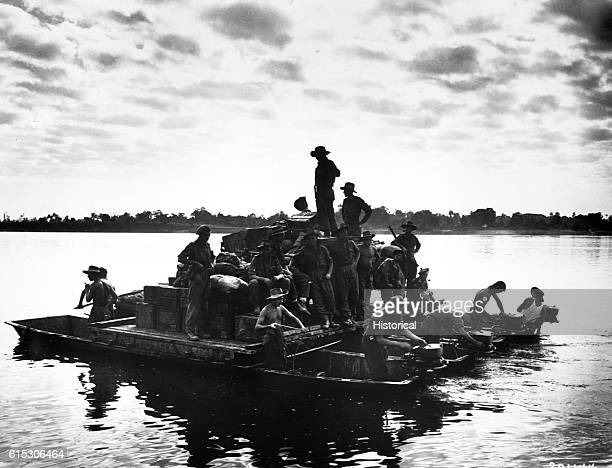 A barge powered by outboard motors crosses the Irrawaddy River near Tigyiang Burma The men their truck and ammunition all make the crossing at once...
