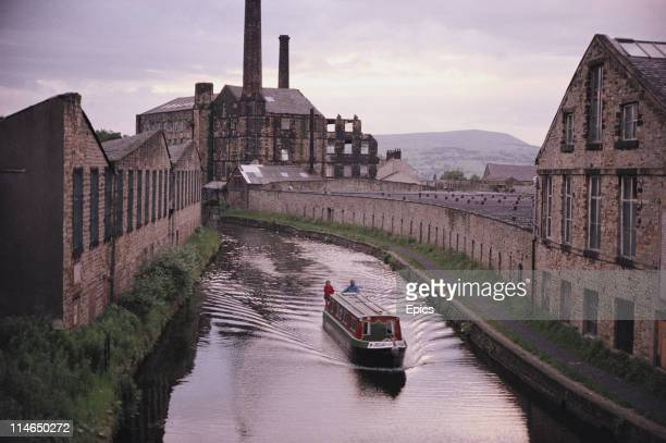 A barge sails along the Leeds and Liverpool canal by Weaver's triangle as seen from the Walker Hey footbridge the clock tower mill can be seen in the...