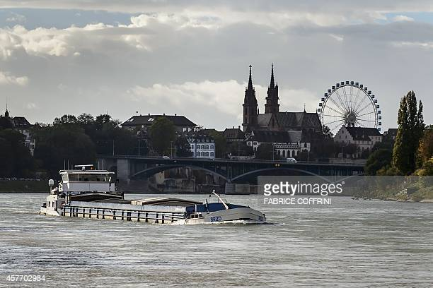 A barge sails on the river Rhine with Basel's cathedral as background on October 22 2014 in Basel AFP PHOTO / FABRICE COFFRINI
