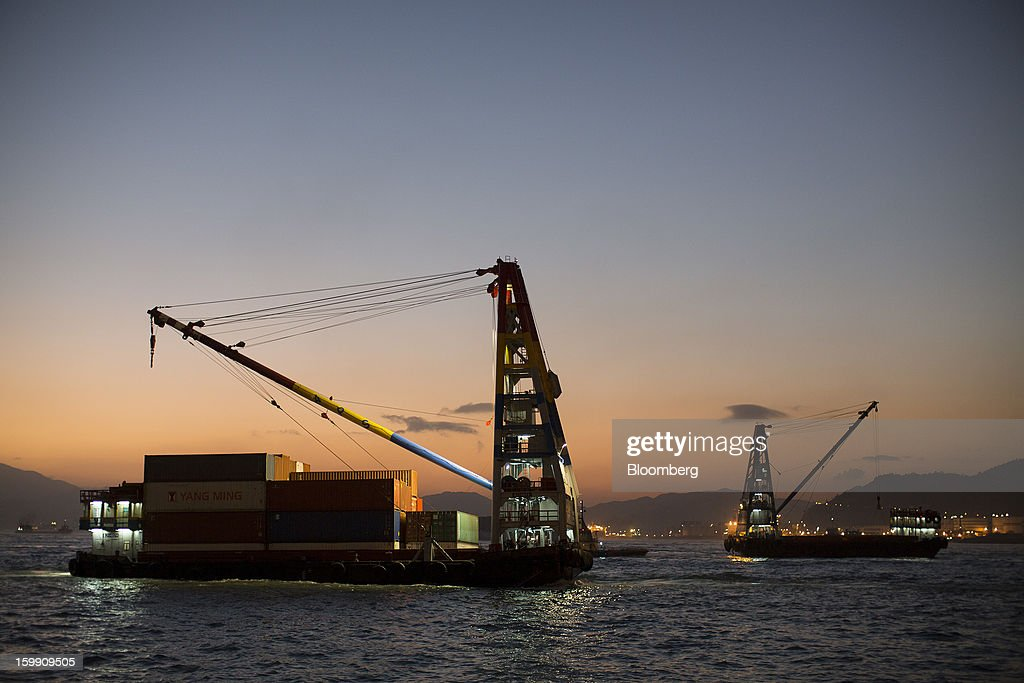 A barge transporting shipping containers, left, sails into the Kwai Tsing Container Terminals as an empty barge sails out in Hong Kong, China, on Monday, Jan. 21, 2013. Hong Kong is scheduled to release export figures for December on Jan. 24. Photographer: Jerome Favre/Bloomberg via Getty Images