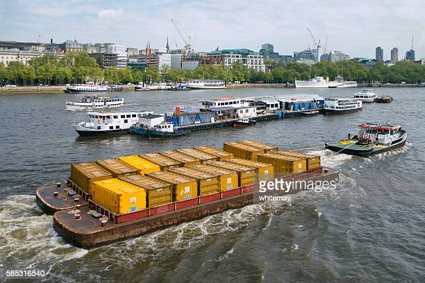 Barges being towed down the River Thames by tug