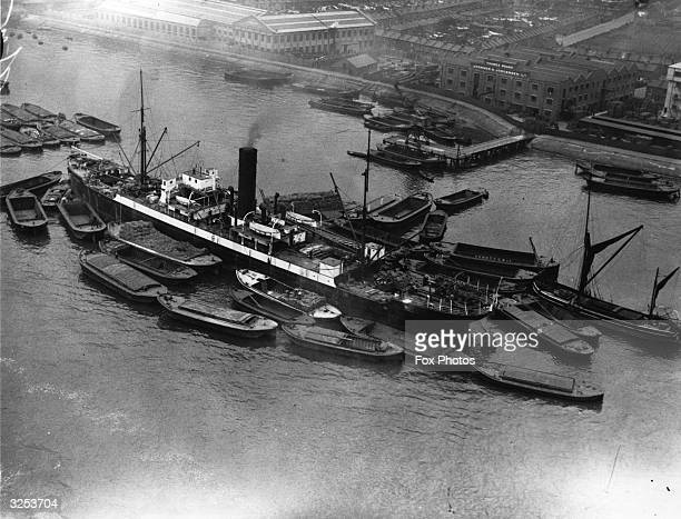 Barges gather round a freight ship to unload its cargo midstream in the Pool of London a busy docklands area of the River Thames