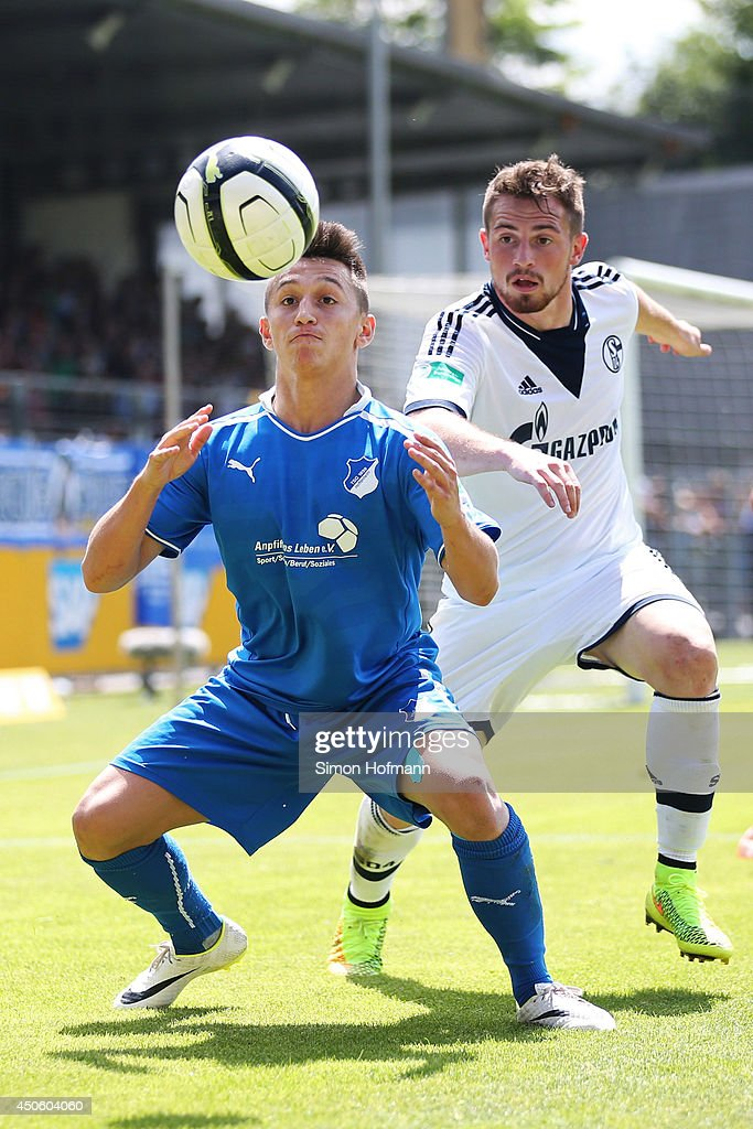 Baris Atik of Hoffenheim is challenged by Maurice Multhaup of Schalke during the A Juniors Bundesliga Semi Final between 1899 Hoffenheim and FC Schalke 04 at Dietmar Hopp-Stadium on June 14, 2014 in Hoffenheim, Germany.