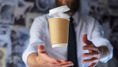 Barista, a bearded young man in a white shirt with a tie trying to catch a paper cup with hot coffee. Background for advertising. Empty place to your logo placement