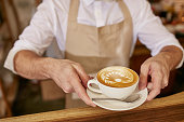 Close-up of man in apron serving coffee while standing in coffee shop. Barista giving you a cup of fresh coffee at cafe.