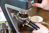 Barista grinding coffee beans using coffee machine