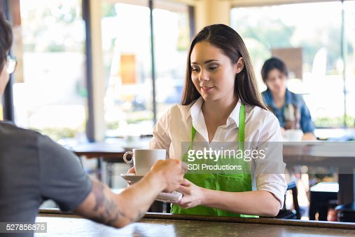 Barista in modern coffee shop delivering beverage to customer's table