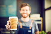 Young barista offering coffee in disposable cup. Smiling waiter is serving drink in coffee shop. Focus is on container.