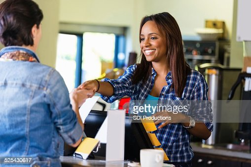 Barista or cashier accepting payment from coffee shop customer