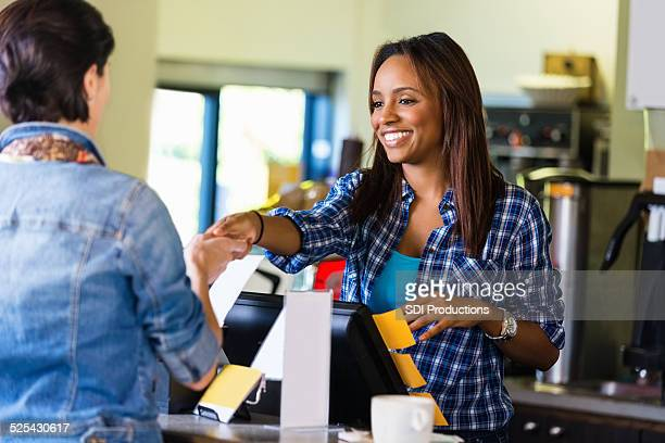 Barista oder Kassierer nimmt Zahlungen von Kunden coffee shop