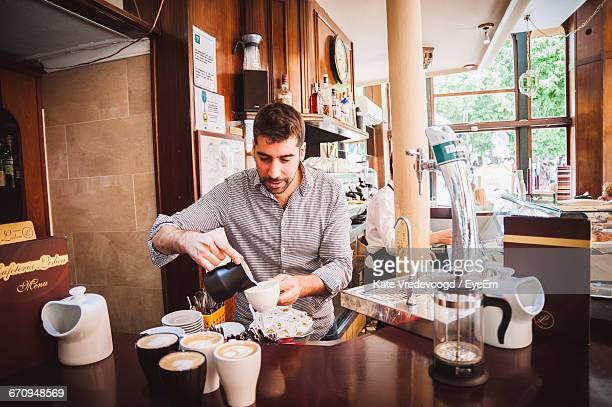 Barista Pouring Cream In Coffee At Cafe