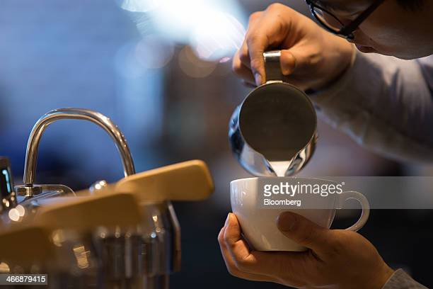A barista pours milk into a cup as he prepares a coffee at the Terarosa Coffee shop in Seoul South Korea on Tuesday Feb 4 2014 South Korea is Asias...