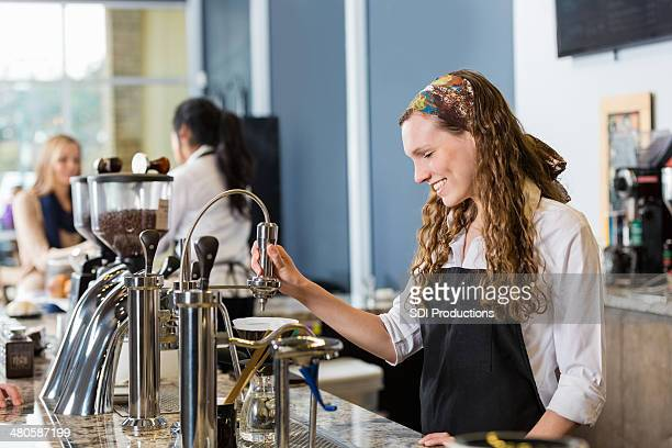 Barista preparing fancy coffee drink in local shop