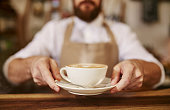 Close up of male barista serving cup of fresh coffee. Cup of coffee in the hands of waiter.