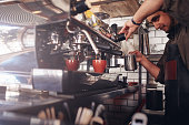 Shot of barista using a coffee maker to make a cup of coffee. Cafe worker preparing a coffee.