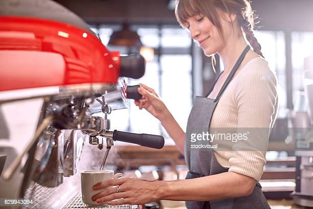 Barista using espresso machine in coffee shop
