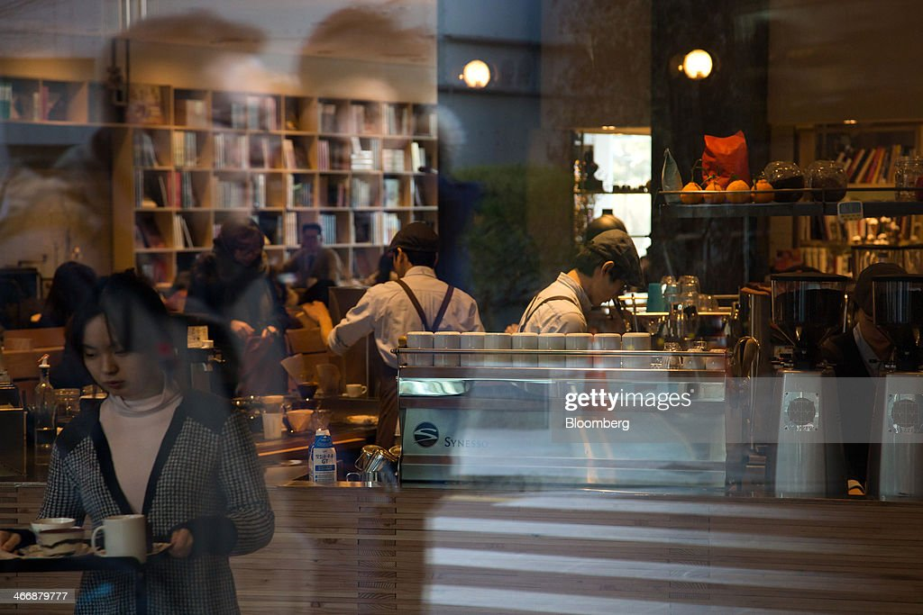 Baristas prepare coffee as pedestrians are reflected in a glass window at the Terarosa Coffee shop in Seoul, South Korea, on Tuesday, Feb. 4, 2014. South Korea is Asias fastest-growing market for arabica coffee, the mild-tasting beans used in premium blends. Photographer: SeongJoon Cho/Bloomberg via Getty Images