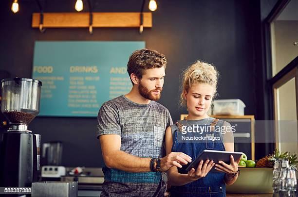 Baristas using digital tablet in coffee shop