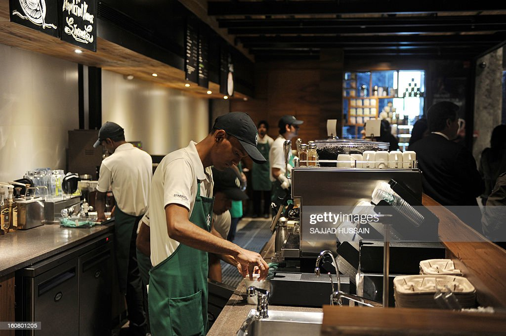 Baristas work behind the counter at the newly-inaugurated Starbucks outlet in New Delhi on February 6, 2013. Starbucks, the world's biggest coffee chain, launched its first outlet in New Delhi on Wednesday with an aim to expand its reach to customers across India.