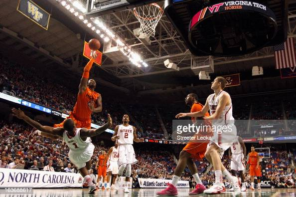 J Barksdale of the Virginia Tech Hokies drives to the basket and over Richard Howell of the North Carolina State Wolfpack during the first round of...