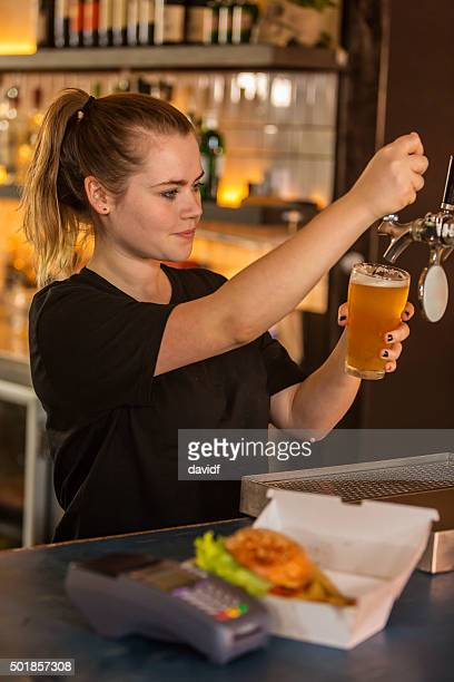 Barmaid Pouring a Beer in a Bar