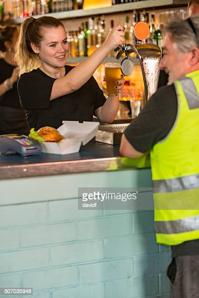 Barmaid Pouring Beer For Workman After Work High Visibility Clothes