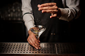 Barman adding salt into a strong martini cocktail decorated with a green olive on the bar