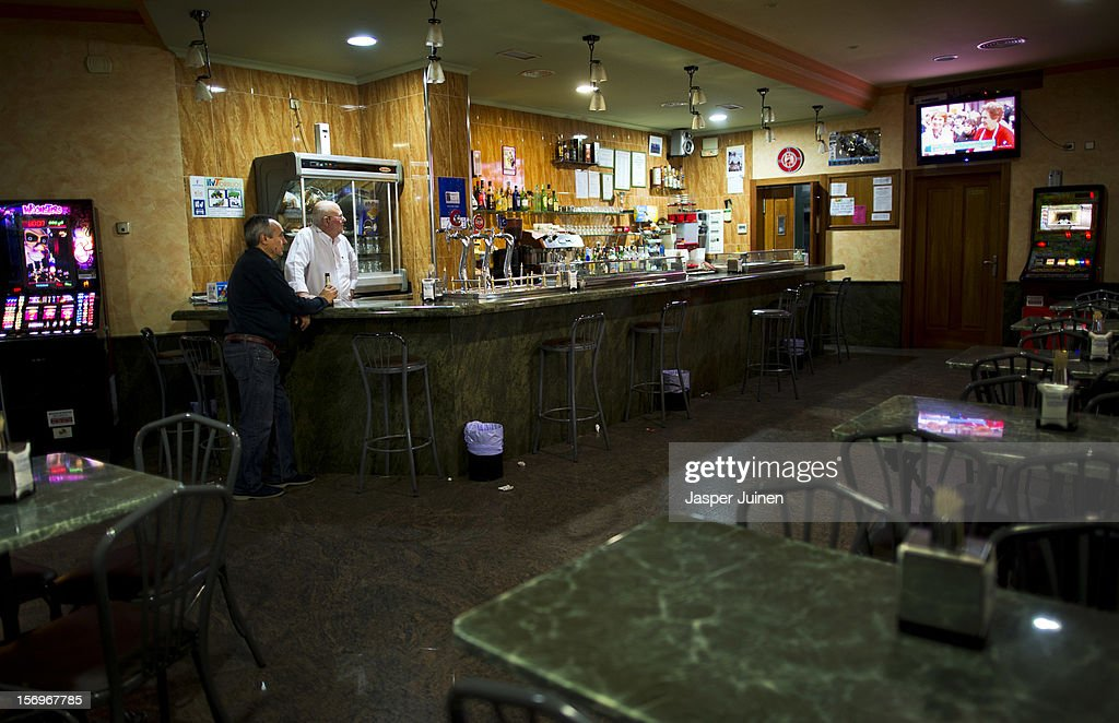 A barman chats with his only customer on a Friday night, a typicall night for Spaniards to hang out, inside his empty bar on November 23, 2012 in Villacanas, Spain. During the boom years, where in its peak Spain built some 800,000 houses a year accompanied by the manufacturing of millions of wooden doors where needed, the people of Villacanas were part of Spain's middle class enjoying high wages and permanent jobs. During the construction boom years the majority of the doors used within these new developments were made in this small industrial town. Approximately seven million doors a year were once assembled here and the factory employed a workforce of almost 5700 people, but the town is now left almost desolate with the Villacanas industrial park now empty and redundant. With Spain in the grip of recession and the housing bubble burst, Villacanas is typical of many former buoyant industrial Spanish towns now struggling with huge unemployment problems.