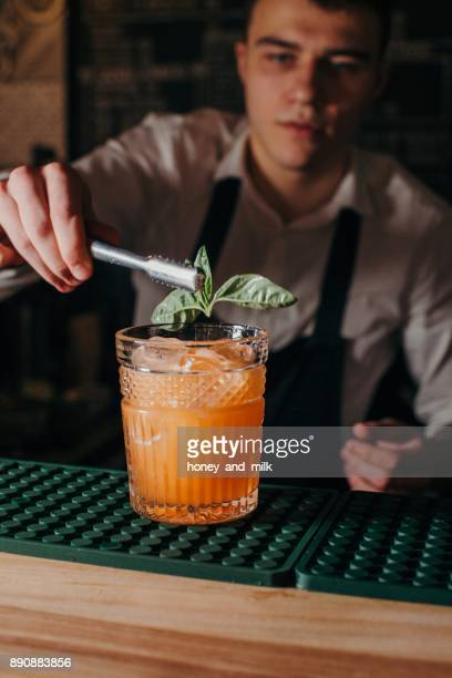 Barman decorating cocktail with basil