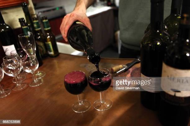 A barman fills glasses to the brim with Medici Ermete Concerto Lambrusco Reggiano a local ruby red sparkling wine made with Lambrusco Salamino grapes...