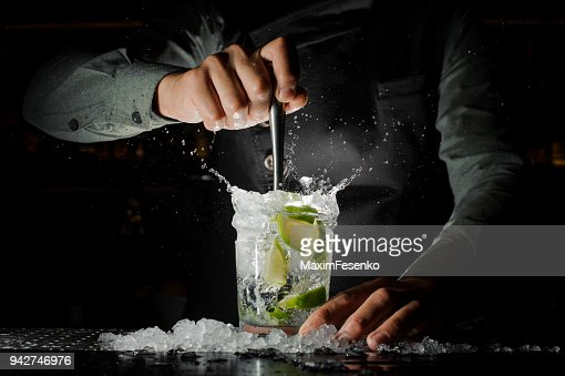 Barman hand squeezing fresh juice from lime making the Caipirinha cocktail : Stock Photo