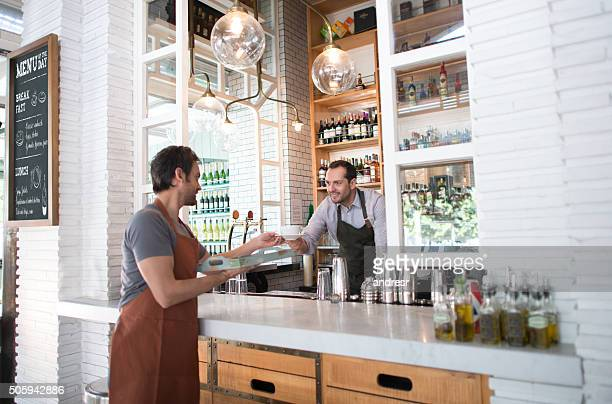 Barman handling order to waiter at a restaurant