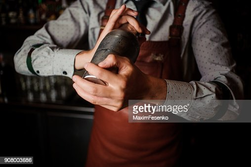 Barman in brown apron shaking the shaker : Stock Photo